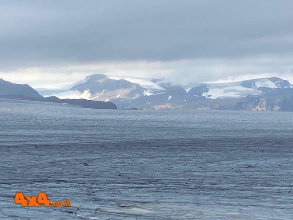 הקרחון גולש ללגונה מרום הפסגות