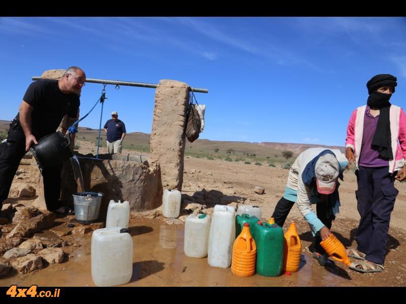 עוזרים לשאוב מים בבאר בקצה מדבר הסהרה